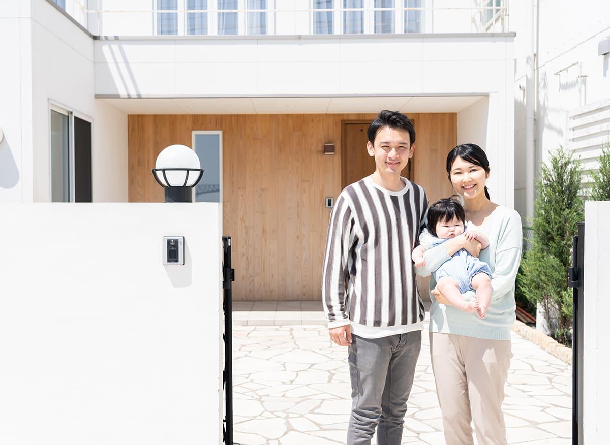 マイホームの前で笑顔の家族